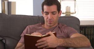 Mann, der zu Hause das Schreiben in seine Zeitschrift sitzt Lizenzfreie Stockbilder