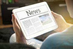 Mann, der zu Hause die Nachrichten auf Tablette liest Stockbild