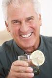 Mann, der zu Hause etwas trinkt Lizenzfreie Stockfotos