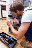 Mann, der zu Hause Kühlschrank repariert Stockfoto