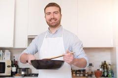 Mann, der zu Hause kocht und Lebensmittel zubereitet Stockbild