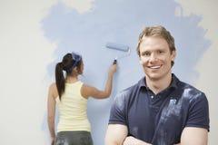 Mann, der zu Hause mit Frauen-Malerei-Wand lächelt stockfotos