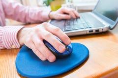 Mann, der zu Hause an seinem Büro des Laptops arbeitet Stockfotografie
