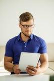 Mann, der zu Hause Tabletten-PC verwendet Stockbilder