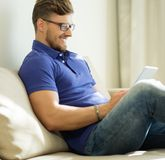 Mann, der zu Hause Tabletten-PC verwendet Stockbild