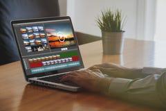 Mann, der zu Hause Video mit einem Laptop redigiert Stockfotografie