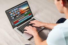 Mann, der zu Hause Video mit einem Laptop redigiert Lizenzfreies Stockbild
