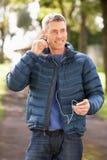 Mann, der zu MP3 hört, während, gehend in Park Lizenzfreies Stockfoto