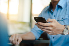 Mann in der zufälligen Form unter Verwendung des Handys im modernen Büro Stockfotos