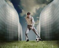 Mann in der zufälligen Klage, die im Fußball nahe dem modernen Gebäude spielt Lizenzfreies Stockfoto