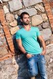 Mann in der zufälligen Kleidung steht gegen eine Ziegelsteinfelsenwand Lizenzfreie Stockfotografie
