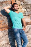 Mann in der zufälligen Kleidung steht gegen eine Ziegelsteinfelsenwand Stockfotografie