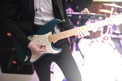 Mann, der zuhause Nahaufnahme der Gitarre auf dem Foto spielt lizenzfreie stockfotografie
