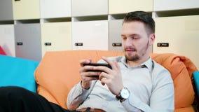 Mann, der zuhause Spiele auf dem Smartphone spielt lizenzfreie stockbilder