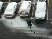 Mann, der zum Auto im Schnee geht. Stockbild