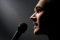 Mann, der zum Mikrofon singt stockfoto
