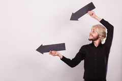 Mann, der zwei Pfeile zeigen die gleiche Richtung hält Stockbilder