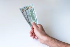 Mann, der zweihundert US-Dollars gibt Stockfoto