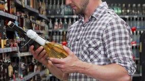 Mann, der zwischen zwei Flaschen Wein wählt stock video footage