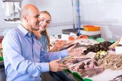 Mann des jungen Mädchens und des Lächelns, der Fische wählt Stockbilder