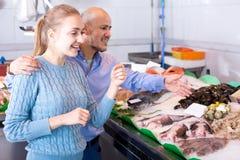 Mann des jungen Mädchens und des Lächelns, der Fische wählt Lizenzfreies Stockfoto