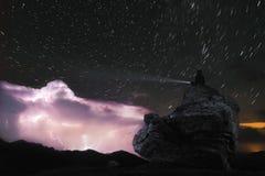 Mann des Nachtfotos A sitzt auf einem Felsen und glänzt eine Taschenlampe am Himmel, auf dem Blitze in den Wolken auf Lizenzfreies Stockbild