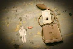Mann des Papiers ist neben dem Gerät für das Messen des Drucks Anschlag, Herzinfarkt abgetönte, inhärente Kratzer Nahaufnahme lizenzfreie stockbilder