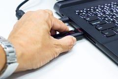 Mann des USB-Blitz-Antriebs an Hand schließen an USB-Port-Einsteckcomputerlaptop für Überweisungsdaten und Unterstützung an Lizenzfreie Stockbilder