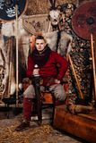 Mann des Viking-Klingengriffklingengestellwiederinkraftsetzungsschmiedeschmiedskriegerswaffenausstattungsaxtschildhaut-Herds eine stockbild