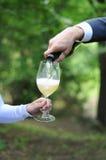 Mann dient seiner Frau Champagner Lizenzfreie Stockfotos