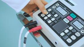Mann drücken die Knöpfe auf dem Bedienfeld des elektronischen Geräts in der Klinik von Hand ein stock video