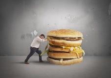 Mann drückt ein Sandwich Lizenzfreies Stockfoto