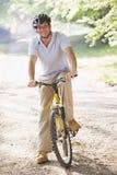 Mann draußen auf dem Fahrradlächeln Stockbild