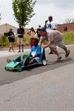 Mann drückt Kinderlenkauto in Atlanta-Seifenkistenrennen Stockbild