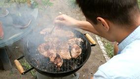 Mann drehen gro?e k?stliche Fleischsteaks um, die ?ber den Kohlen auf Grill braten stock video footage