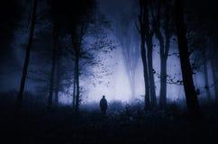 Mann in Dunkelheit frequentiertem Holz lizenzfreie stockfotos