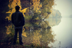 Mann durch Herbstsee Stockfotografie