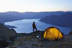 Mann durch See und Zelt an der Dämmerung Lizenzfreies Stockbild