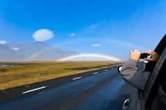Mann in einem Auto schießt isländische Landschaft mit doppeltem Regenbogen Stockfotografie