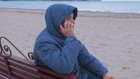 Mann in einem Blau hinunter die Jacke, die auf einer Bank auf dem Sandstrand sitzt, Handy nennt und auf Antwort wartet stock video footage