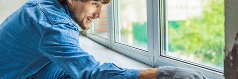 Mann in einem blauen Hemd tut Fensterinstallation FAHNE, LANGES FORMAT stockfoto