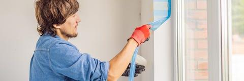 Mann in einem blauen Hemd tut Fensterinstallation FAHNE, LANGES FORMAT lizenzfreies stockfoto