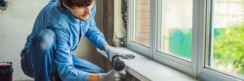 Mann in einem blauen Hemd tut Fensterinstallation FAHNE, LANGES FORMAT lizenzfreie stockfotos