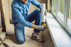 Mann in einem blauen Hemd tut Fensterinstallation Unter Verwendung eines Montageschaums lizenzfreie stockbilder