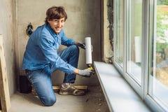 Mann in einem blauen Hemd tut Fensterinstallation Unter Verwendung eines Montageschaums stockbilder