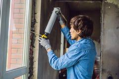 Mann in einem blauen Hemd tut Fensterinstallation Unter Verwendung eines Montageschaums lizenzfreie stockfotografie