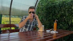 Mann in einem Café sprechend am Telefon stock video footage