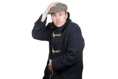 Mann in einem dunkelgrauen Mantel, der Kappe hält Lizenzfreies Stockbild