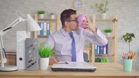 Mann in einem Hemd, das an einem Laptop im Büro mit einem Sparschwein sitzt stock video footage