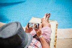 Mann in einem Hut, der auf einem Ruhesessel mit einem Smartphone liegt Stockfoto